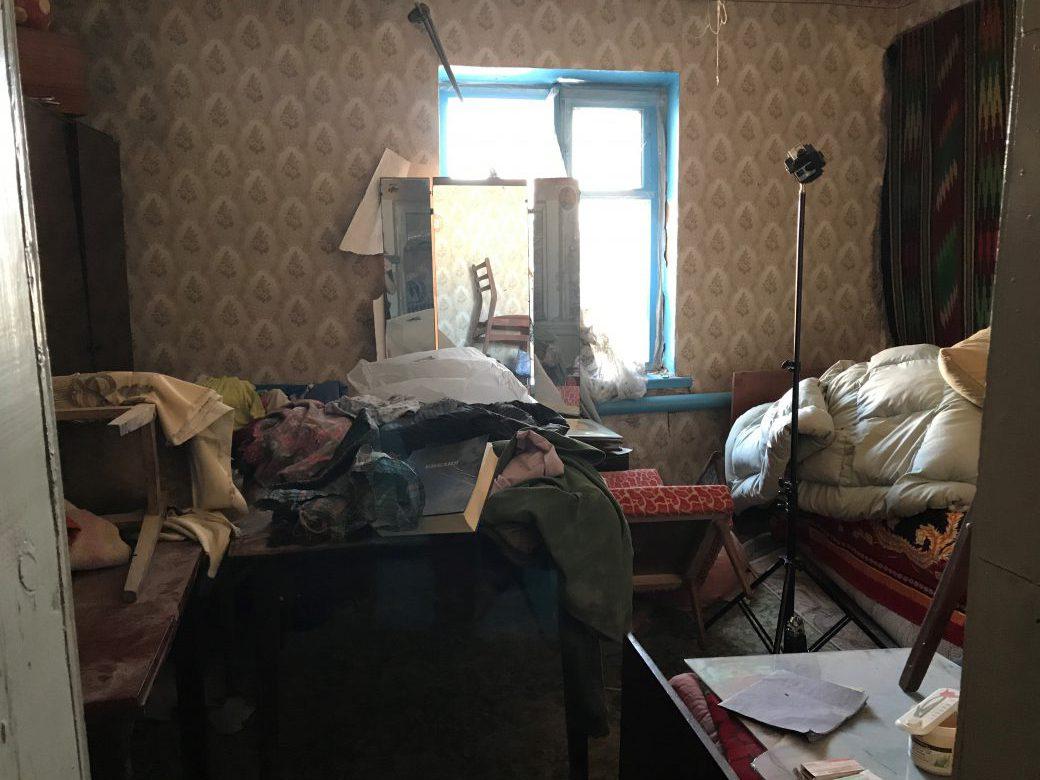 Im zerstörten Wohnzimmer zeigt Olena Ivanivna ein Foto ihres verstorbenen Mannes.